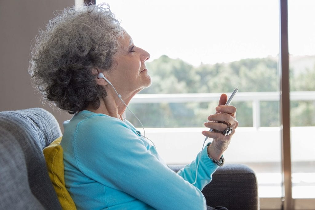 a relaxed older woman wearing earphones enjoying music.  Music therapy concept