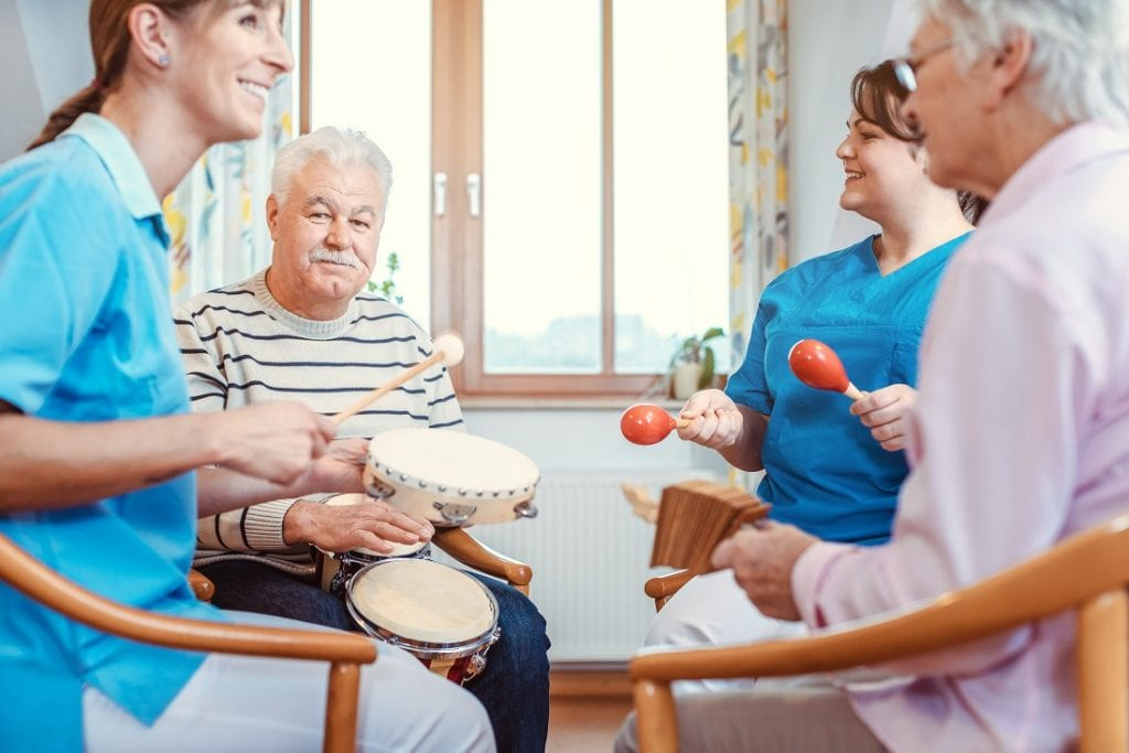 Seniors in the nursing home play music with rhythm musical instruments with the help of caregivers, as a music therapy session.