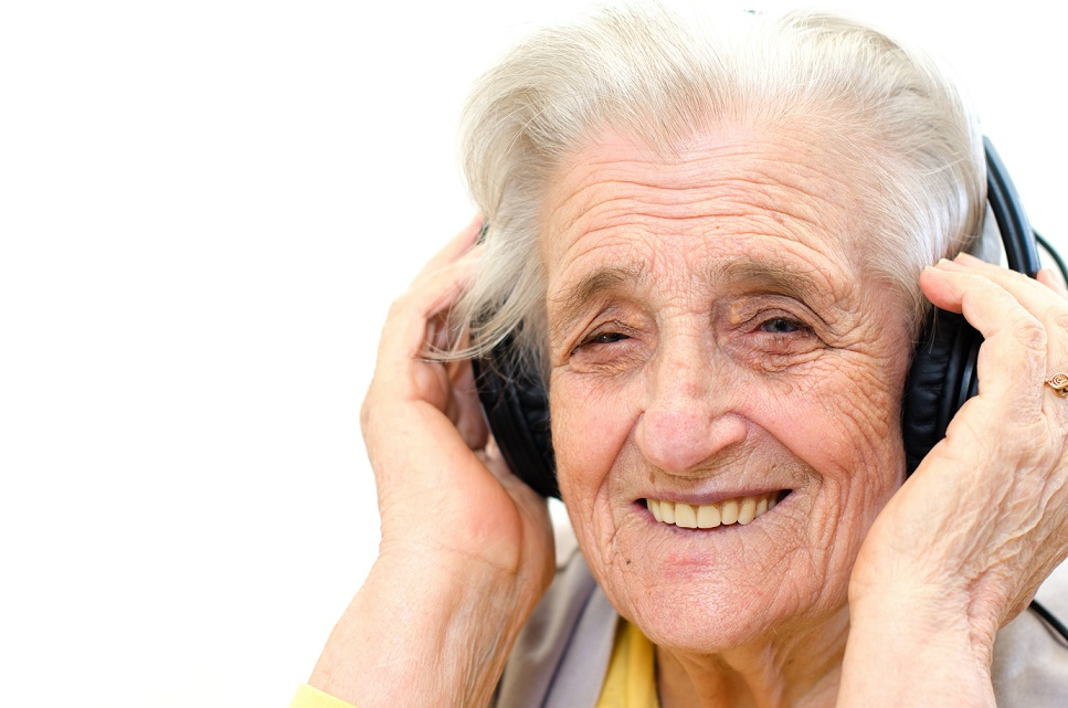 A senior woman listening to music with a headphone. She is smiling.