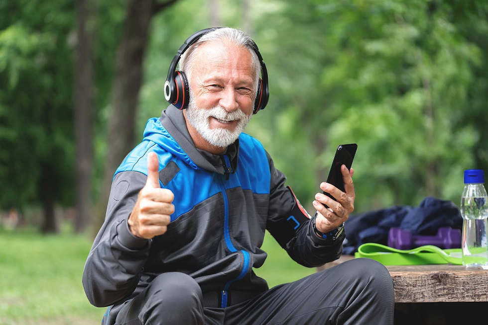 A senior man is listening to music during exercise.