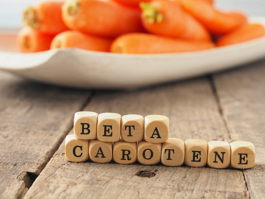 Wooden dices with the words beta carotene and fresh carrots in the back