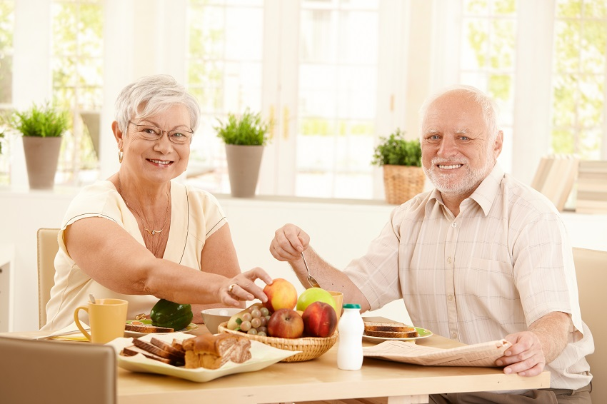 a senior couple eating fruits at the table